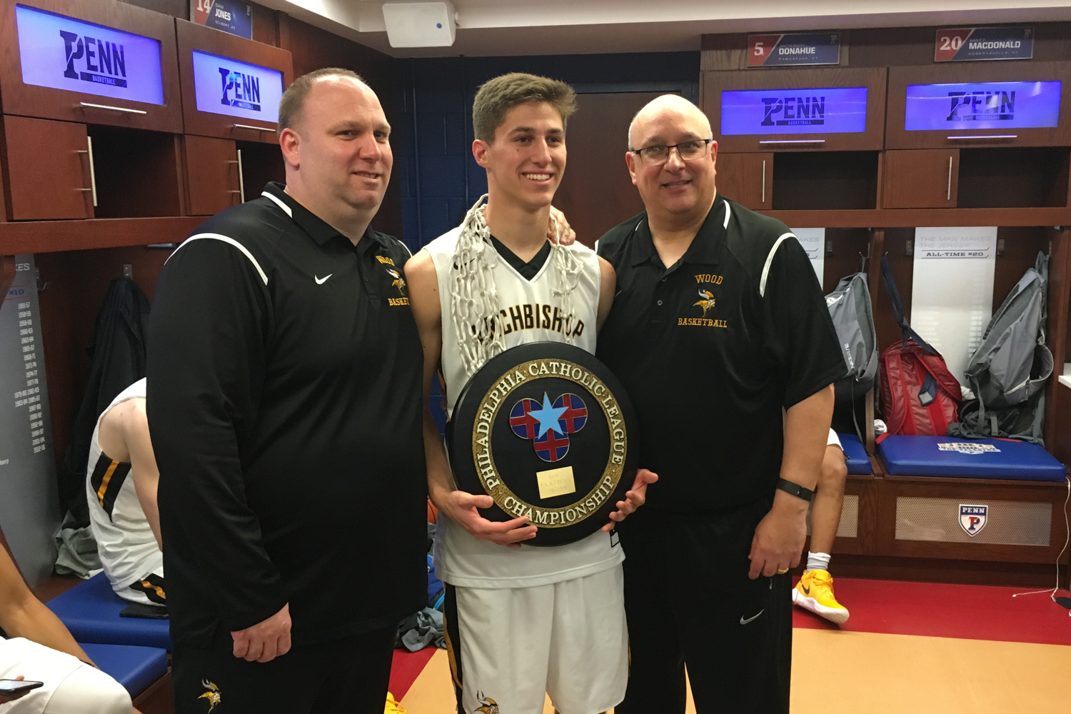 Coach Chris Roantree, Collin Gillespie, and Head Coach John Mosco - in the locker room at the Palestra after winning the 2017 Philadelphia Catholic League (PCL) Championship.